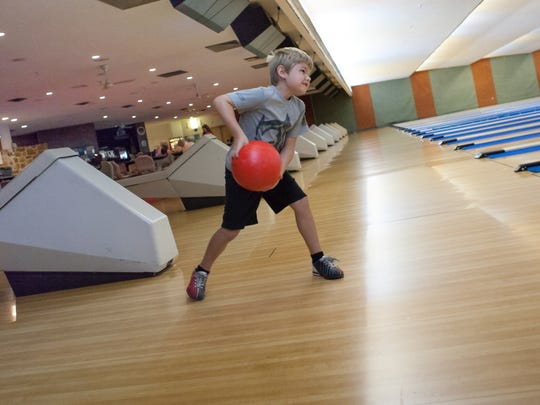 Seven-year-old Bradey Scout bowls with friends and family the day before his operation.