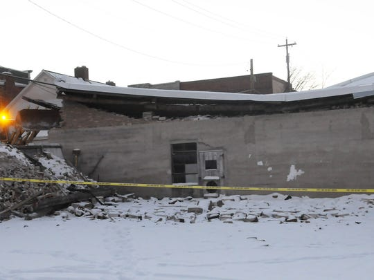 A crew shores up a storage section Monday of a collapsed roof at Bayside Bargains, 14 S. Madison Ave.