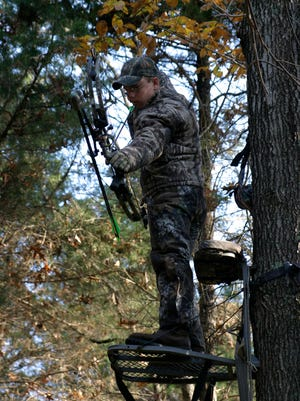 Bowhunter in a tree stand drawing his bow