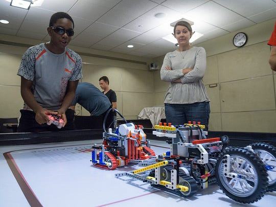 Teen Librarian Elizabeth Phou watches the battle. Mannie Stephens is at the controls of his Lego robot Blark.