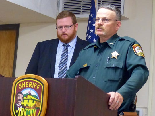 District Attorney John Sugg, left, listens at a press