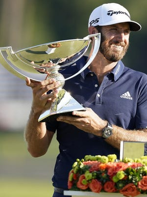 Dustin Johnson holds up the FedEx Cup trophy after winning the Tour Championship on Monday.