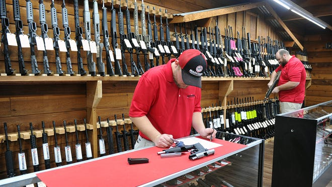 Mitchaletty Baio, left, and Jason Lavender of Marksman Firearms and Outfitters, inventory stock at the new gun store on Kemp Blvd. The shop's grand opening will be Saturday December 2.