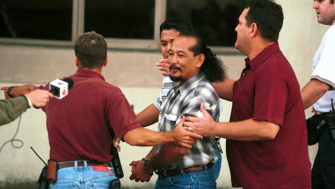 In this January 2000 file photo, former Sen. Angel Santos is taken away by U.S. Marshals after being sentenced in U.S. District Court in Hagåtña.