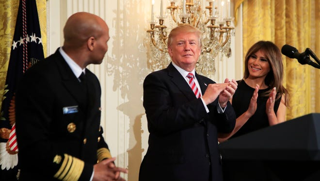 President Trump and first lady Melania Trump applaud Surgeon General Jerome Adams during a National African American History Month reception in the East Room of the White House Tuesday.