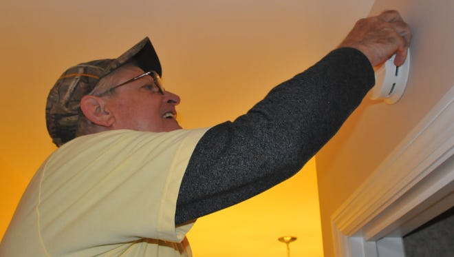 Les Robinson installs a smoke detector as part of the American Red Cross' Home Fire Safety campaign.