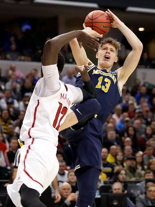 FILE - In this March 19, 2017, file photo, Michigan's Moritz Wagner (13) shoots over Louisville's Mangok Mathiang (12) during the first half of a second-round game in the men's NCAA college basketball tournament, in Indianapolis. Wagner's versatility has been on full display in the NCAA Tournament. The 6-foot-11 German was the key to Michigan's victory over Louisville that put the Wolverines in the Sweet 16. (AP Photo/Jeff Roberson, File)