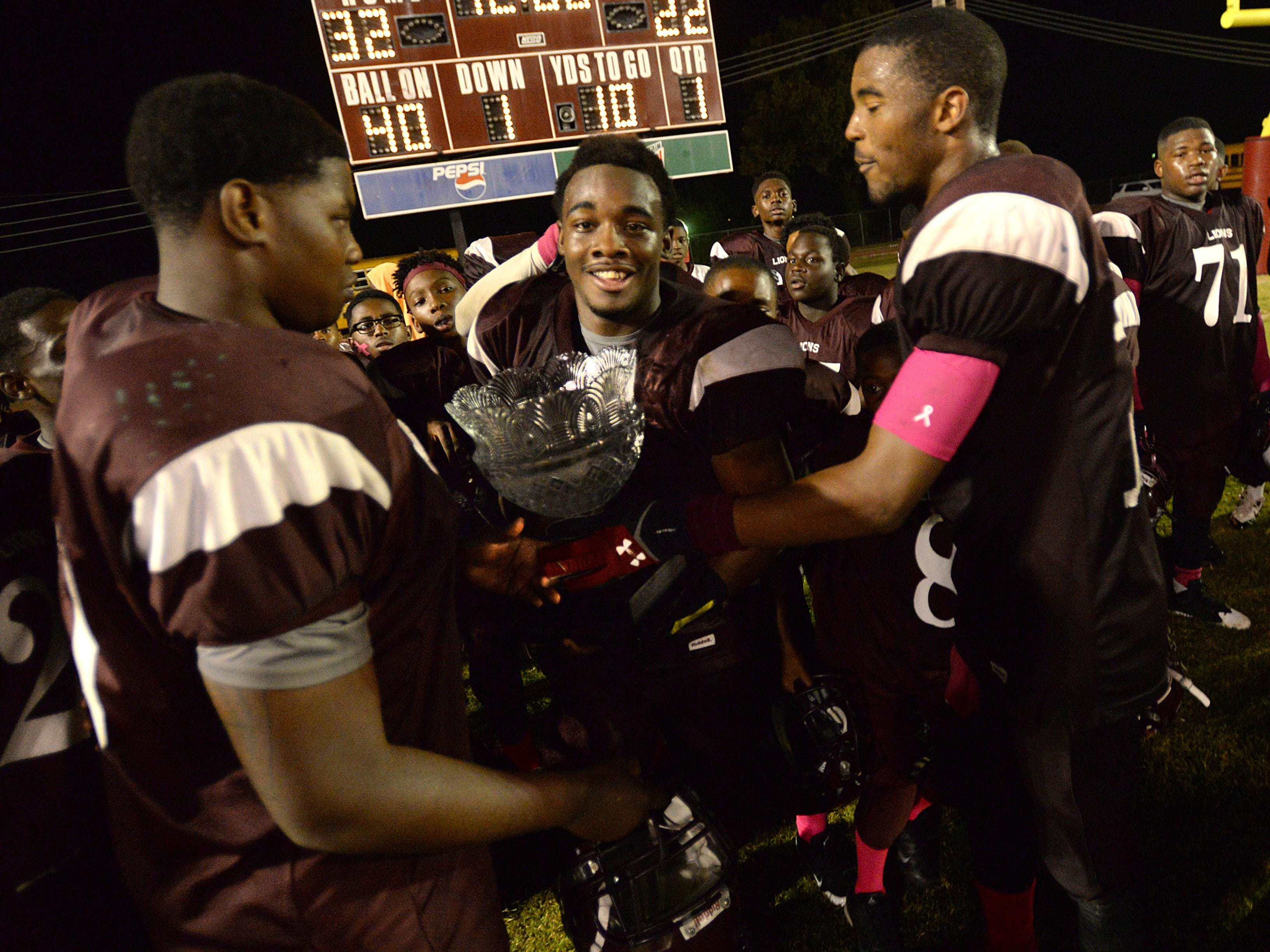BTW's Joshua Horton carries the Soul Bowl trophy after his team defeated Green Oaks, 32-22 in the 2014 Soul Bowl.