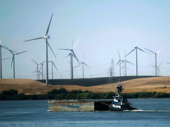 Wind turbines are seen along the Sacramento River near the city of Rio Vista.