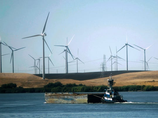 California passed a law that requires electricity comes from carbon-free energy such as solar and wind power by 2045. Wind turbines are seen along the Sacramento River near the city of Rio Vista. AP PHOTO