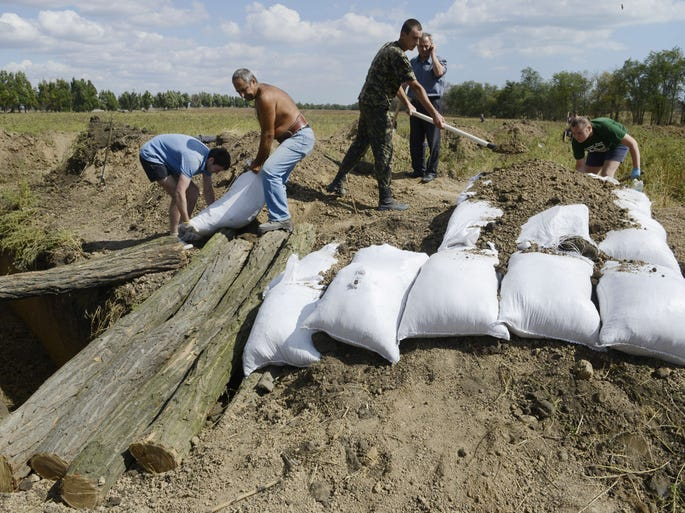Residents of Mariupol, Ukraine, dig trenches and make fortifications with sandbags on Aug. 29. They are assisting Ukrainian troops in organizing their defense on the outskirts of the city.