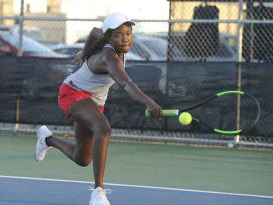 Cooper's Taja Lawrence lunges to hit a backhand to