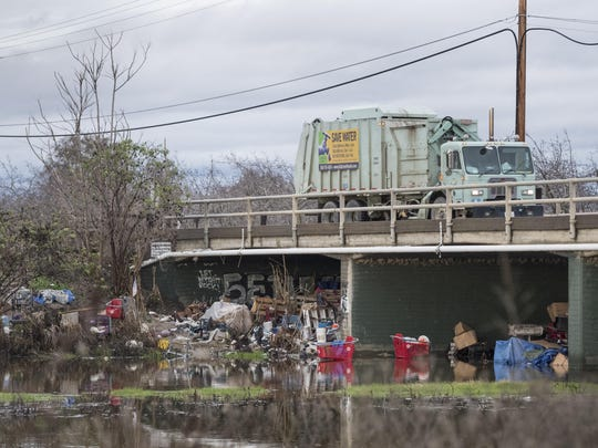 More than half a dozen shopping carts, some partially submerged in water, surrounded by building materials, tarps, furniture, a bicycle and other debris are gathered around the Ben Maddox Way bridge over the St. Johns River on Jan. 5, 2017.
