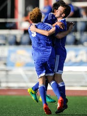 Memorial's Sam Bonano (9) Marky Lara (19) and Andrew Cross (13) celebrate one of Cross' two goals  during the Class 2A state championship against Chesterton at Carroll Stadium in Indianapolis on Saturday. Memorial beat Chesterton 2-1.