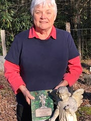"""Gail Palmer stands with her book """"Cemeteries of the Smokies"""" at the tombstone featured on the book's front."""