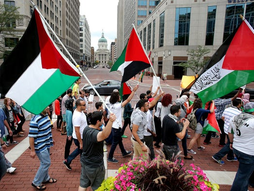 Pro-Palestinian signs and flags are held while walking around Monument Circle during a solidarity protest against Israel, Saturday, July 19, 2014, in Indianapolis.