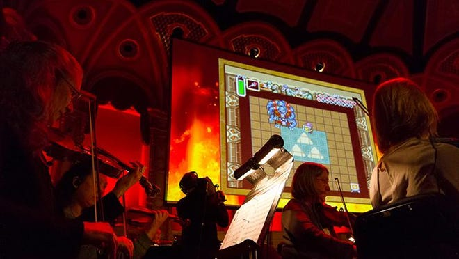 """An orchestra performs music from the video game series as footage from """"The Legend of Zelda: A Link to the Past"""" is projected on a large screen during """"The Legend of Zelda: Symphony of the Goddesses — Master Quest."""" (Date and venue unknown) (Andrew Craig / Provided by Gentry Brown of TriplePoint PR on behalf of Jason Michael Paul Productions)"""