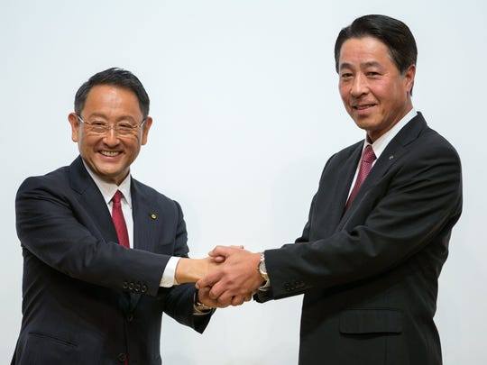 Toyota Motor Corp. President Akio Toyoda (L) and Mazda Motor Corporation President and CEO Masamichi Kogai join hands during a news conference in Tokyo, Japan, August 4, 2017.