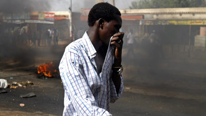A Sudanese man covers his mouth from heavy smoke after protesters burnt tires to close the highway to northern cities amid a wave of unrest over the lifting of fuel subsidies by the Sudanese government, in Kadro, 15 miles (24.14 kilometers) north of downtown Khartoum on Wednesday.