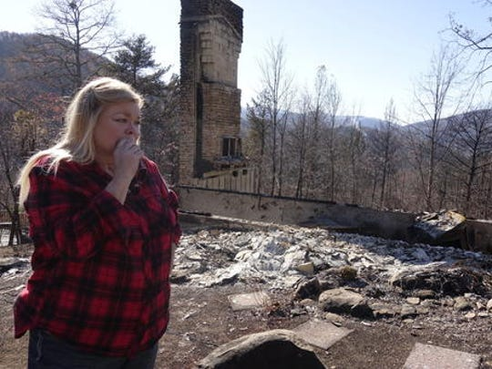 Tammy Sherrod views the remains of her home in the Roaring Fork neighborhood of Gatlinburg, Tenn., Friday, Dec. 2, 2016. Residents on Friday, were getting their first look at what remains of their homes and businesses in Gatlinburg, after a wildfire tore through the resort community on Monday, Nov. 28.