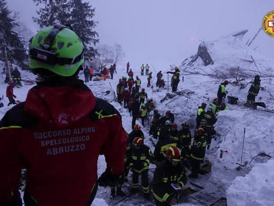 """Rescuers work at the avalanche-hit Rigopiano hotel, Saturday, Jan. 21, 2017. After two days huddled in freezing cold, tons of snow surrounding them in the wreckage of the avalanche-demolished hotel, survivors greeted their rescuers Friday as """"angels."""" Among the 10 people pulled out alive was a plucky 6-year-old who just wanted her favorite cookies."""