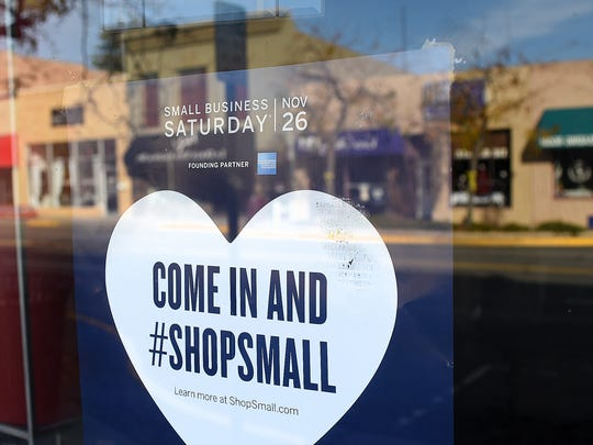 A poster advertising Small Business Saturday is taped in the window of the Chile Pod in downtown Farmington on Thursday.