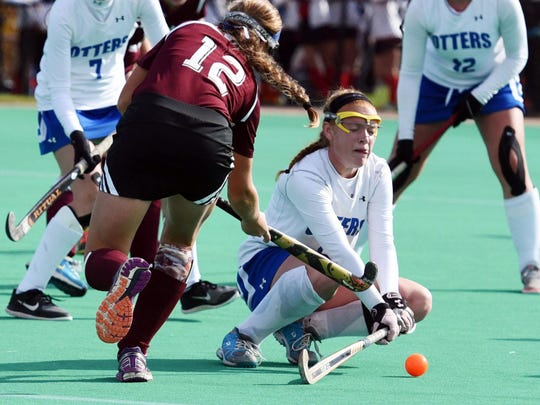 Otter Valley's Allison Lowell, center, battle for the ball during the second half of the field hockey Division II state championship game at the University of Vermont on Oct. 31.