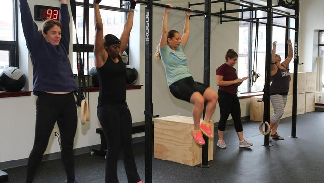 Class participants hang from bars during a cross-fit workout at Foundry Fitness in Ossining June 2, 2015.