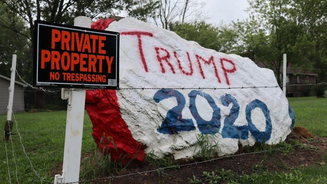The owners of this rock painted to support President Donald Trump's re-election put a fence around it last week following two recent incidents of vandalism. The rock sits along state Route 183 near Minerva.