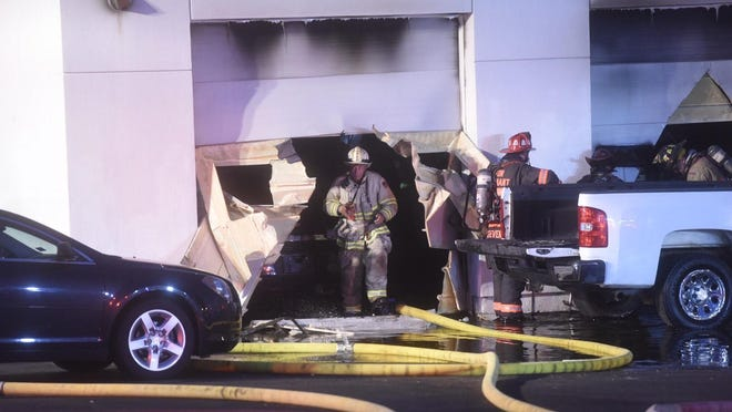 A firefighter emerges from a service bay at Hilltop Chevrolet Friday night.