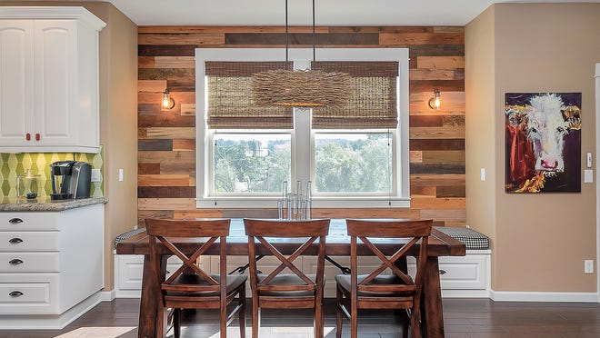 This dining room remodeled by Dale's Remodeling now features barn wood accent walls, layered lighting and cow art.