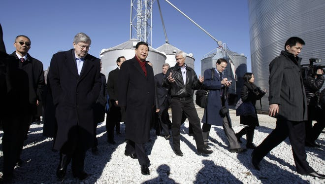 Chinese Vice President Xi Jinping, center, flanked by Gov. Terry Branstad, left, and Maxwell farmer Rick Kimberley, takes a tour of Kimberley's farm on Thursday, Feb. 16, 2012. Xi looked at equipment, asked about marketing and learned about drying and storing corn.