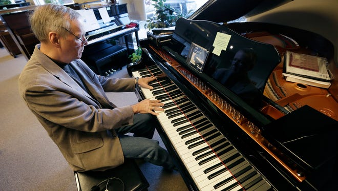 In this Dec. 3, 2014, photo, Jim Foster plays a grand piano in his Foster Family Music Center piano store in Bettendorf, Iowa. The number of stores dedicated to selling pianos is dwindling across the country as fewer people take up the instrument and those who do opt for a used piano or a less expensive electronic keyboard.
