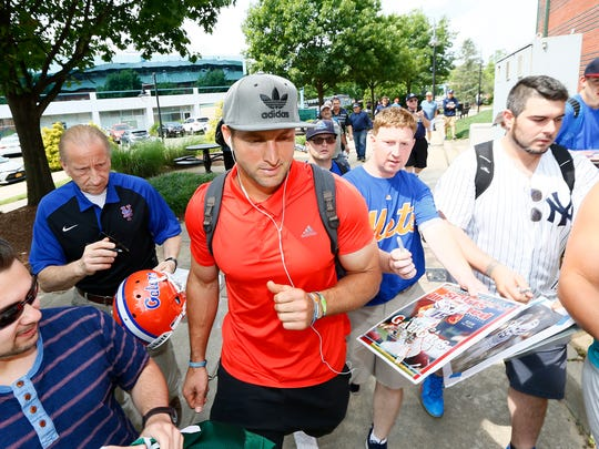 After getting off the team bus, Tim Tebow walks by