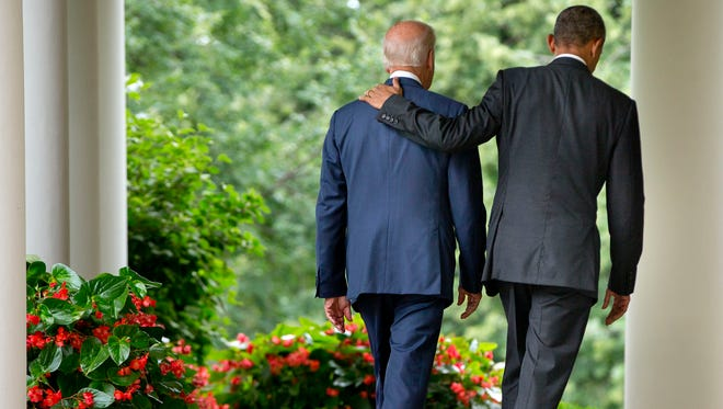 President Barack Obama walks with Vice President Joe Biden back to the Oval Office of the White House in Washington, Thursday, June 25, 2015, after speaking in the Rose Garden after the Supreme Court upheld the subsidies for customers in states that do not operate their own exchanges under President Barack Obama's Affordable Care Act.