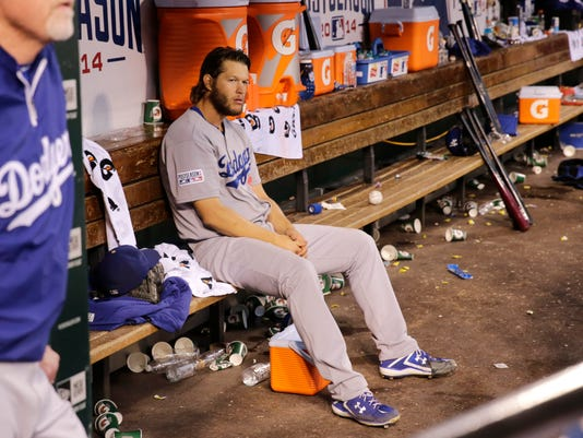 Los Angeles Dodgers starting pitcher Clayton Kershaw sits in the dugout after getting taken out of the game in the seventh inning of Game 4 of baseball's NL Division Series against the St. Louis Cardinals, Tuesday, Oct. 7, 2014, in St. Louis. (AP Photo/Charles Rex Arbogast)
