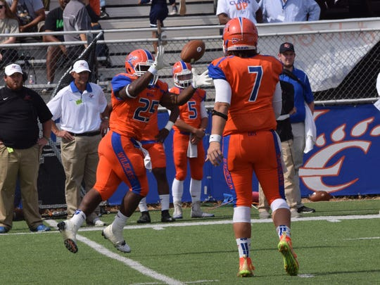 Louisiana College  quarterback Easton Melancon (7, right) passes to Aurren Cooksey (25, left) Saturday, Oct. 17, in a NCAA Division III game against the University of Mary-Hardin Baylor (Texas) at Wildcat Stadium in Pineville, La.