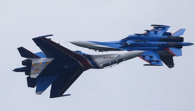 Sukhoi Su-27 Flanker fighters of the Russkiye Vityazi (Russian Knights) aerobatic show team are seen performing in 2015.