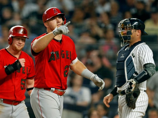 May 26, 2018; Bronx, NY, USA; Los Angeles Angels center fielder Mike Trout (27) celebrates a two-run home run in front of New York Yankees catcher Austin Romine (28) during the fourth inning at Yankee Stadium.
