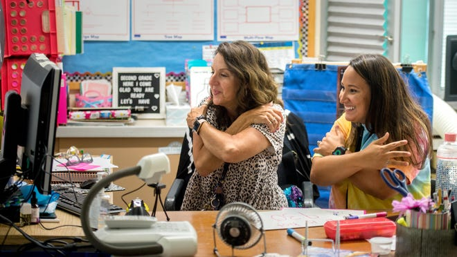 Northmoor Primary School second-grade teacher Robin Tandeski, left, and special education teacher Katie Hobin give virtual hugs to their students at the end of an online class on Monday, the first day of remote learning in the Peoria Public Schools District.