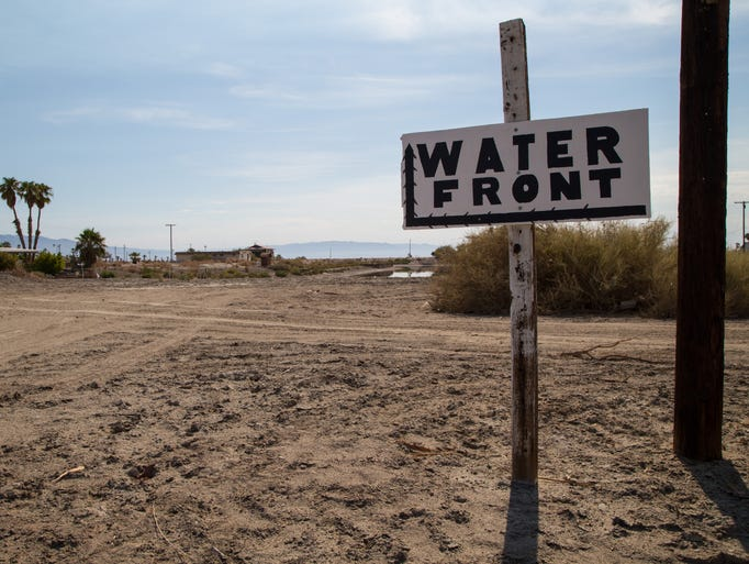 A sign for the waterfront points in the direction of the receding shoreline in Desert Shores, Calif., July 24, 2014.