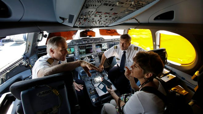 Airbus test pilot Frank Chapman, left, and test flight engineer Bruno Bigand, center, sit in the cockpit as they describe the new Airbus A350 XWB passenger airplane at Newark Liberty international airport in New Jersey on July 16, 2015.