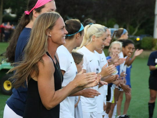 Former Monmouth University women's soccer player Christie Rampone stands with the Hawks on Monday night before their game against Seton Hall.