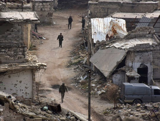 Syrian pro-government troops walk on a street in Aleppo's