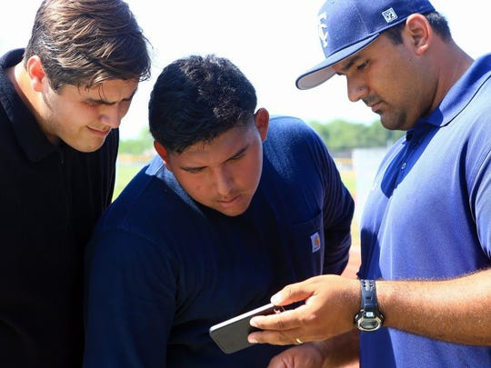 GABE HERNANDEZ/CALLER-TIMES Carroll head track coach Rigo Morales (right) shows video of their throws to Eric Ramirez (center) and Hunter Bowers during practice Wednesday at Carroll High School.