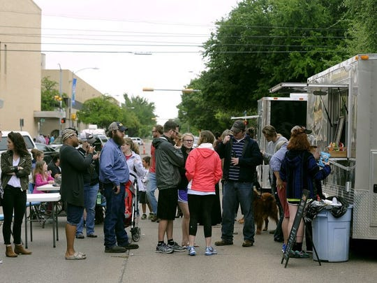Thomas Metthe/Reporter-News People wait in line for lunch from the Toasted Traveler and Wayne's World food trucks during Big Day Downtown on Saturday, April 16, 2016.