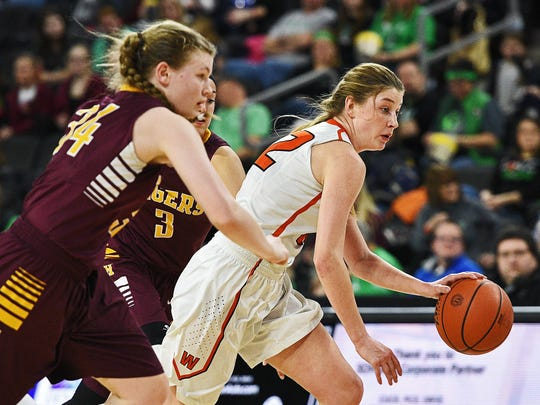 Washington's Anna Goodhope (22) drives between Harrisburg defenders during the 2016 state tournament at the Denny Sanford Premier Center in Sioux Falls.