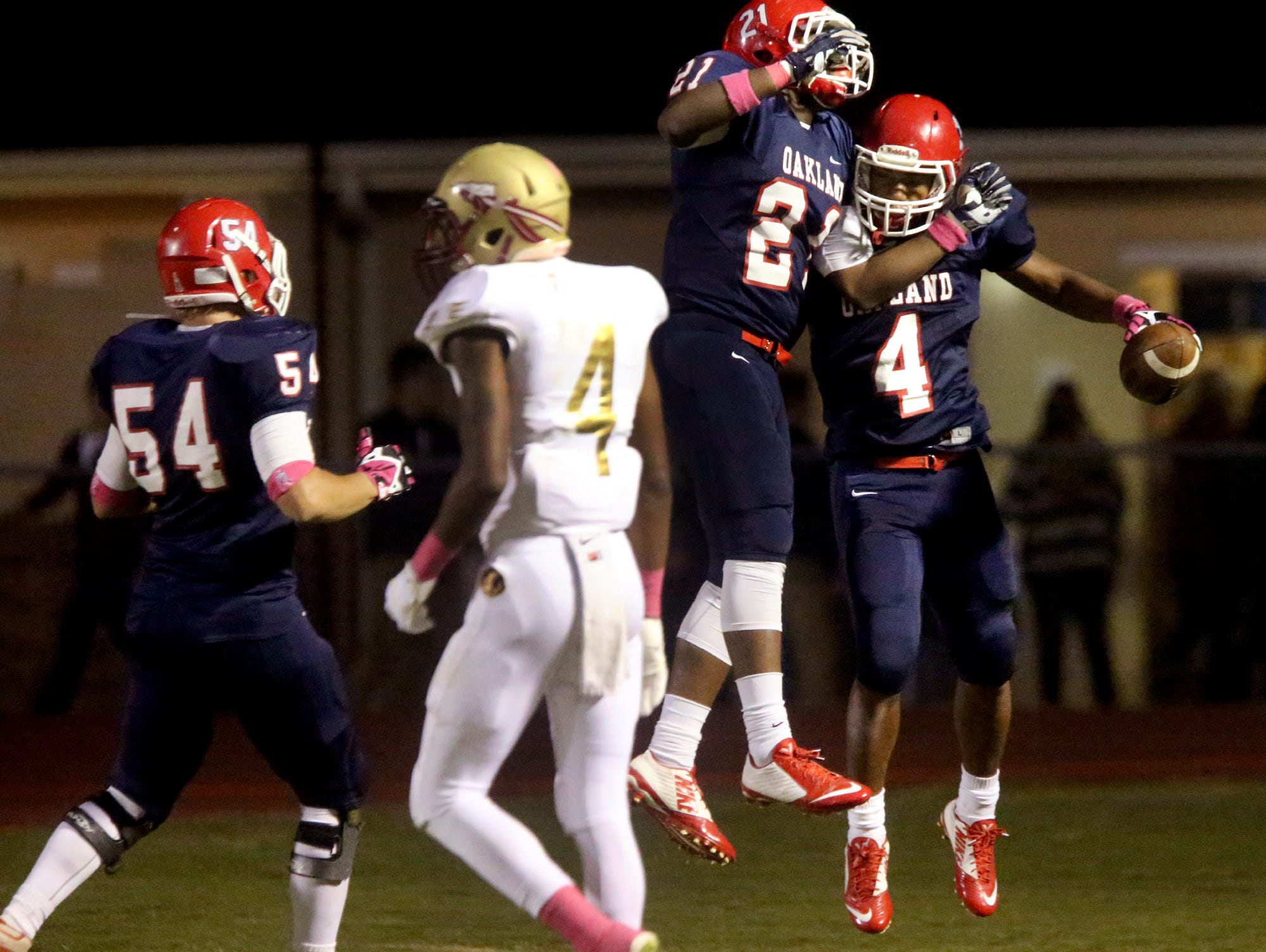 Oakland's Justice Dingle (21) and Lazarius Patterson (4) celebrate Oakland's first touchdown of the game against Riverdale at Oakland, on Friday Oct. 16, 2015. Oakland's Jacob Frazier (54) moves in to join the celebration as Riverdale's Marquise Cantrell (4) walks off.