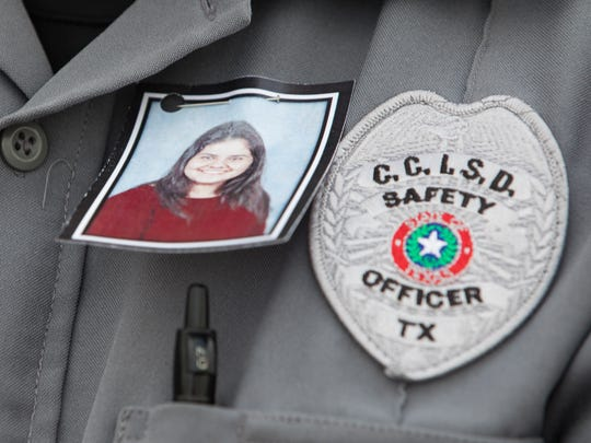 A CCISD safety officer wears a photo of King High School student Rai-ane Garza pinned on his shirt Wednesday, March 28, 2018, during  a vigil. Rai-ane was killed by a hit-and-run driver Tuesday, March 27, 2018, just off campus.