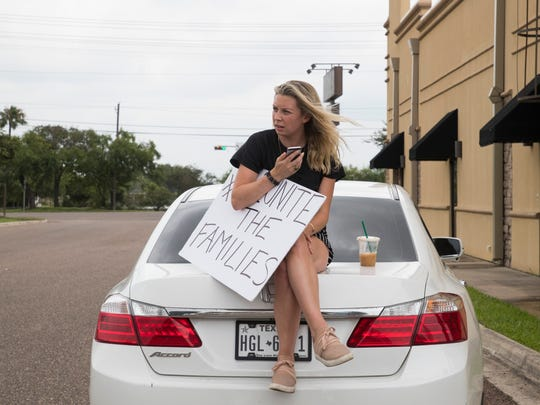 Nicole Enriquez, 26, from Dallas, sits on her car holding